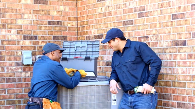 Latin and African American blue collar workers fixing ac unit in backyard