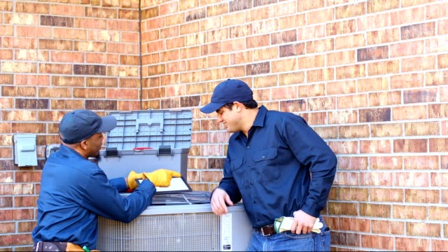 latin and african american blue collar workers fixing ac unit in backyard - craftsperson stock videos and b-roll footage