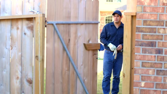 latin blue collar worker coming through backyard gate with tools ready to work - gate stock videos & royalty-free footage