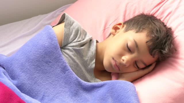 lateinischer junge schläft im bett - schlafzimmer stock-videos und b-roll-filmmaterial
