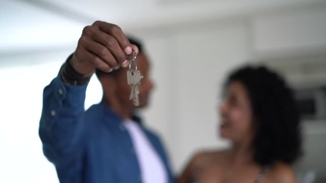 latin couple holding the keys of their new house - computer key stock videos and b-roll footage