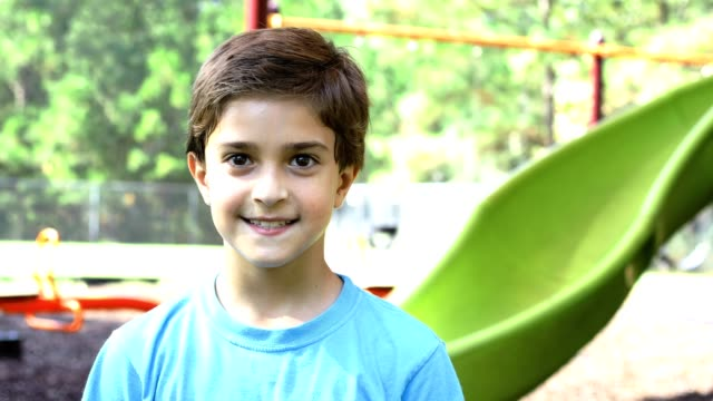 latin descent boy playing on school playground. - solo un bambino maschio video stock e b–roll