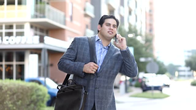 latin descent business man on the go in downtown city. - laptop bag stock videos and b-roll footage