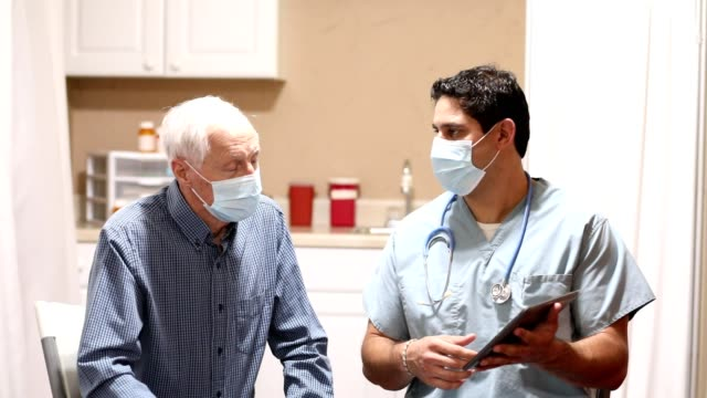 covid-19: latin descent doctor and senior adult patient, masks. - clinica medica video stock e b–roll