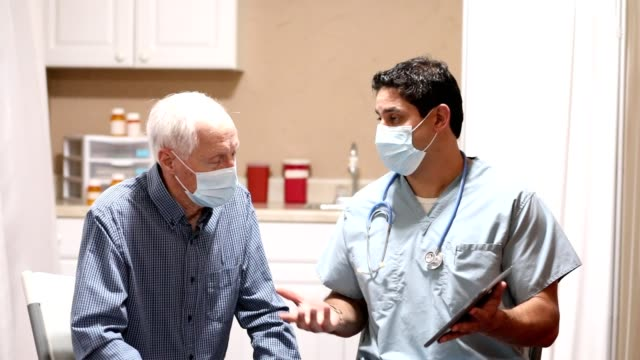 covid-19: latin descent doctor and senior adult patient, masks. - number 3 stock videos & royalty-free footage