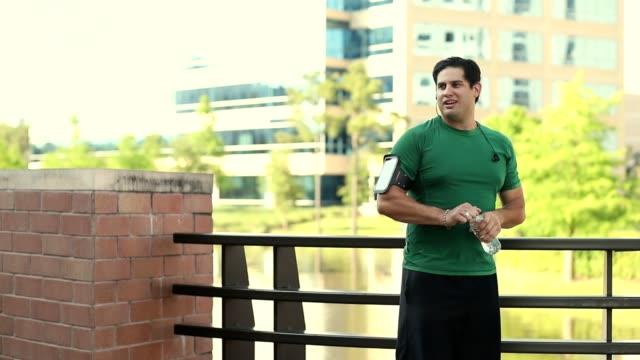 latin descent man exercising in downtown city area. - misurare il polso video stock e b–roll
