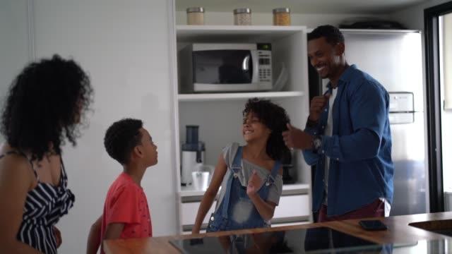 vidéos et rushes de famille latine dansant ensemble dans la cuisine - deux parents