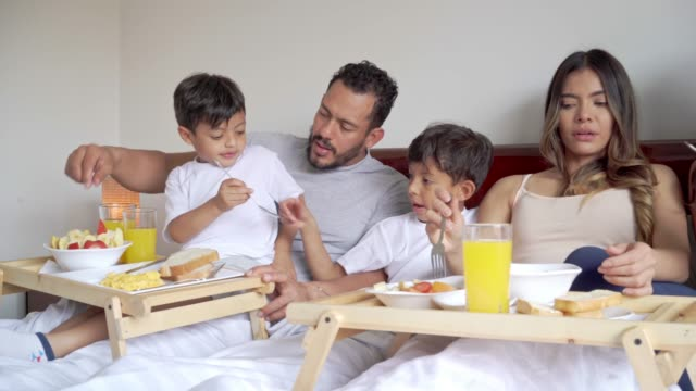 latin family of five people having breakfast together in bed - five people stock videos & royalty-free footage
