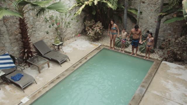 vídeos y material grabado en eventos de stock de latin family playing in pool of holiday home - mérida méxico