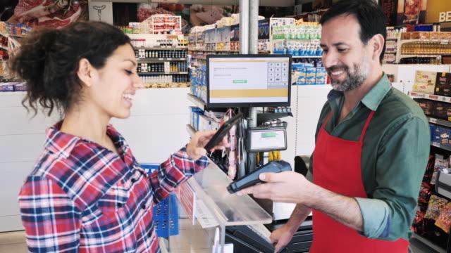 vídeos y material grabado en eventos de stock de compras familiares latinas en supermercado - mujer adulta pagando con tarjeta sin contacto - pago por móvil