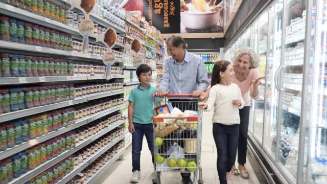 vidéos et rushes de achats de famille latinedans le supermarché - aînés avec des petits-enfants dans le supermarché - fraîcheur