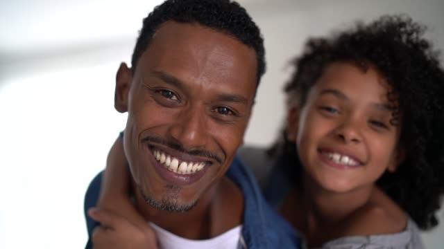 vídeos de stock, filmes e b-roll de pai latin que prende sua filha em casa-retrato - família de duas gerações