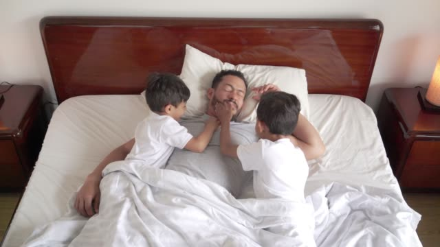 latin father sleeping with his two children in bed. his children try to wake him up by tickling him and pulling on him. - i love you stock videos & royalty-free footage