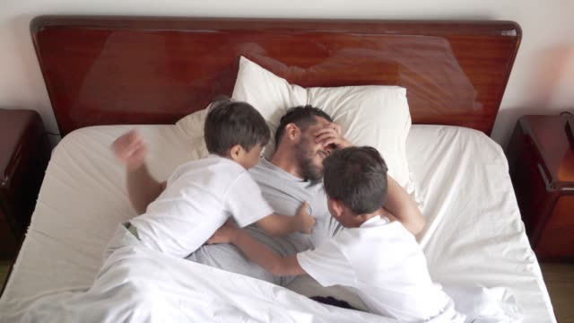 latin father sleeping with his two children in bed. his children try to wake him up by tickling him and pulling on him. - bedroom stock videos & royalty-free footage