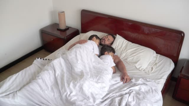 latin father sleeping with his two children in bed. one of his sons lies on him while caressing his back - bedtime stock videos & royalty-free footage