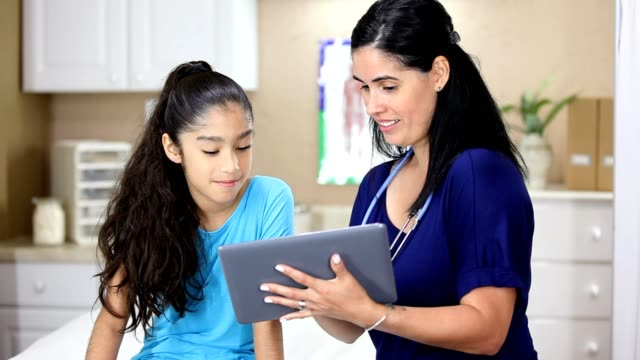 Latin female doctor holding digital tablet.  She is doing a sports check up on young Latin female patient.
