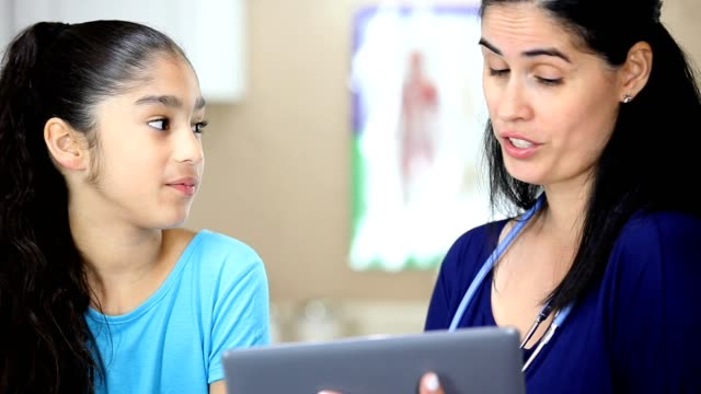 latin female doctor holding digital tablet.  she is doing a sports check up on young latin female patient. - clinic stock videos & royalty-free footage