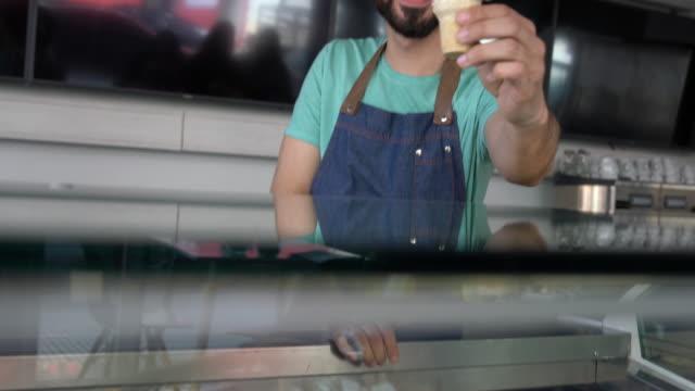 vídeos y material grabado en eventos de stock de mujer latina feliz mirando a la cámara, en una heladería - helado condición