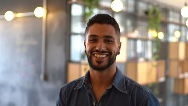 latin male portrait standing at work studio - sorridere video stock e b–roll