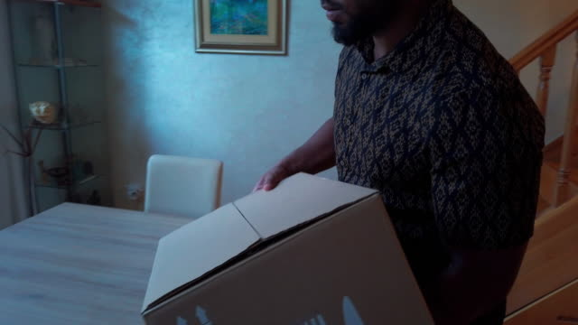 latin man carrying box with groceries and placing on the table - meal box stock videos & royalty-free footage