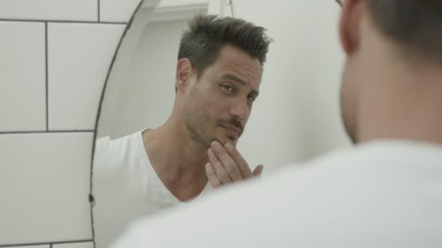 stockvideo's en b-roll-footage met latin man checking hair in bathroom mirror - generatie z