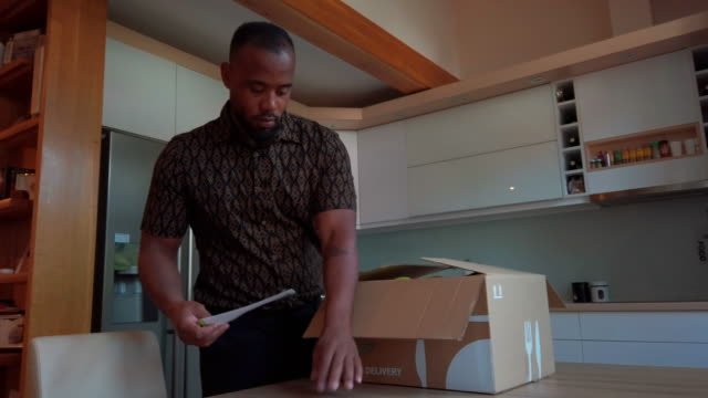 latin man taking out groceries out of box - meal stock videos & royalty-free footage