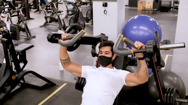 vídeos y material grabado en eventos de stock de hombre latino usando aparato de gimnasio con máscara protectora - gym