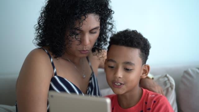 vídeos de stock, filmes e b-roll de matriz e filho latin usando a tabuleta digital em casa - utilizar o tablet