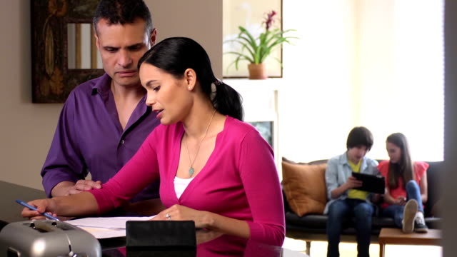 Latin Parents Discuss Home Finances with Kids in Background