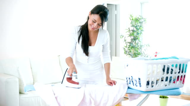 Latin woman ironing clothes at home