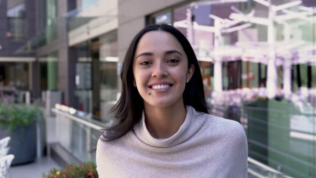 vidéos et rushes de la femme latine regarde l'appareil-photo qui l'enregistre et sourit - 20 24 years