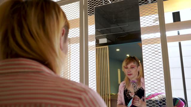 latinsk kvinna med lesbisk sexuell läggning rätar upp sig och tittar i spegeln och sätter på sin gay pride flagga mask - spektrum bildbanksvideor och videomaterial från bakom kulisserna