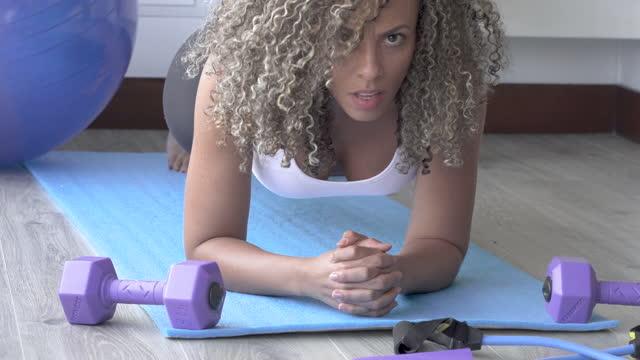 vídeos de stock, filmes e b-roll de mulher latina realiza exercícios de alongamento de dentro de sua casa - brown hair