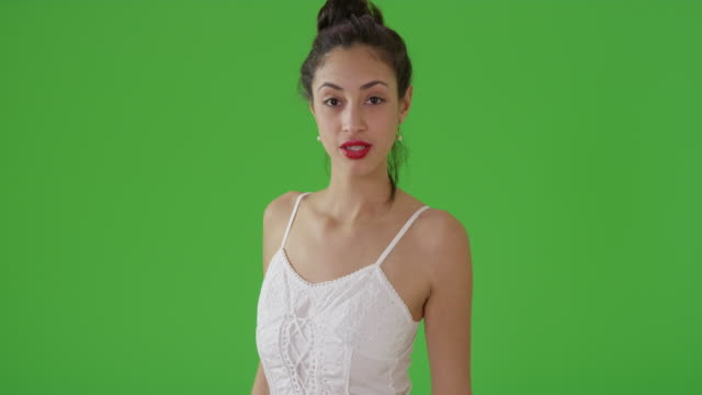 a latin woman poses for a portrait in a sun dress on green screen - オフビート点の映像素材/bロール