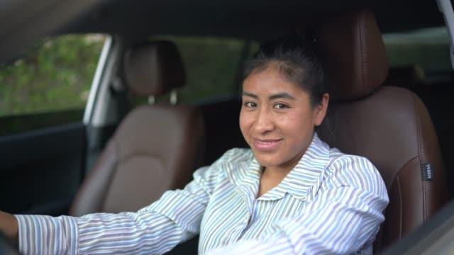 vídeos y material grabado en eventos de stock de mujer latina sentada en el asiento del conductor, conduciendo coche - taxista