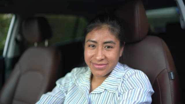 Latin woman sitting in driver's seat, driving car
