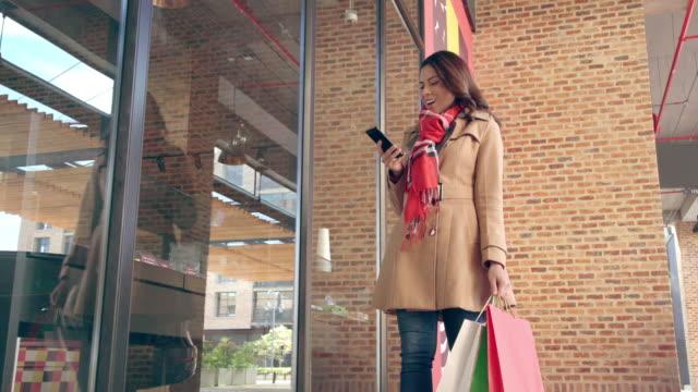 vídeos y material grabado en eventos de stock de mujer latina caminando sola a través de un centro comercial mientras mira los escaparates con su teléfono en la mano - escaparate de tienda