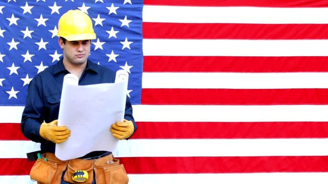 latin worker in uniform and hard hat.  he stands before an american flag. - tool belt stock videos and b-roll footage