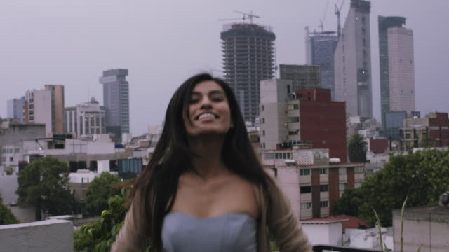 Latin young adult female on rooftop with skyline