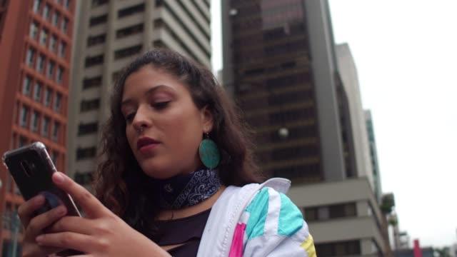 vídeos de stock, filmes e b-roll de mulher nova latin que usa o telemóvel durante a hora do rush - adolescentes meninas