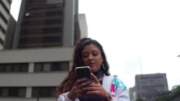Latin young woman using cellphone during rush hour