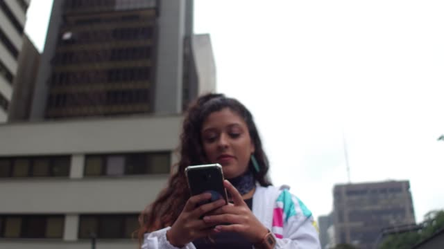 latin young woman using cellphone during rush hour - handheld stock videos & royalty-free footage