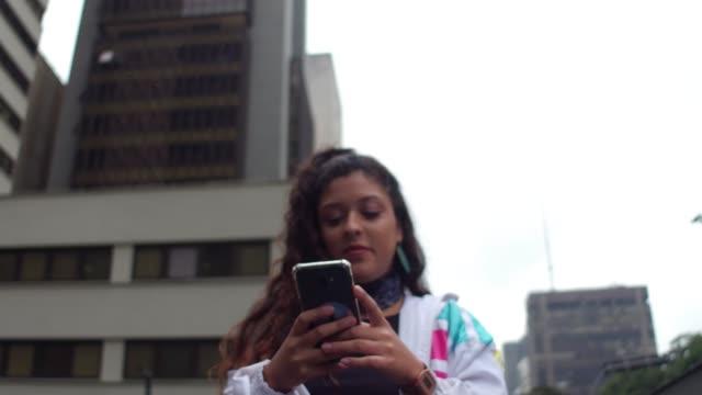 lateinische junge frau mit handy während der hauptverkehrszeit - teenage girls stock-videos und b-roll-filmmaterial