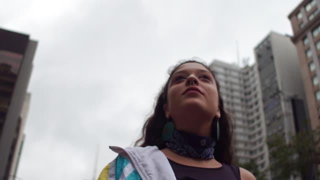 vídeos de stock, filmes e b-roll de mulher nova latin que anda na cidade - low angle view