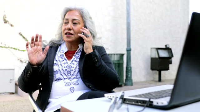 latina businesswoman using laptop at cafe - baby boomer stock videos & royalty-free footage
