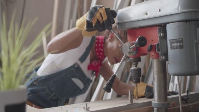 Latina Carpenter Drilling Plank In Her Workshop