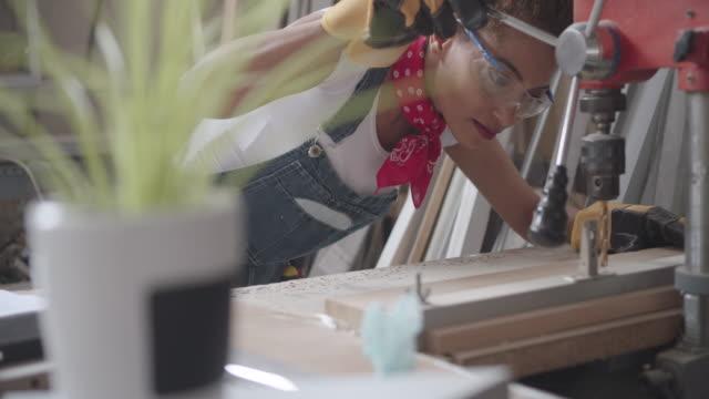 Latina Carpenter perfuração prancha em sua oficina