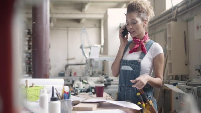 Latina Carpenter spricht am Telefon In Ihren Workshop
