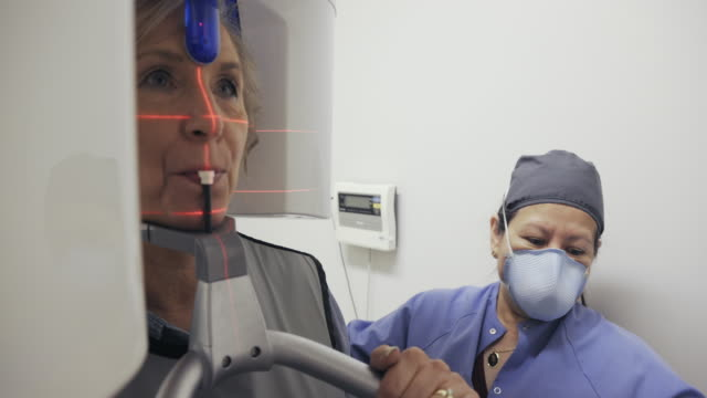 a latina dental hygienist in her fifties wearing a face mask prepares a caucasian woman in her sixties for dental x-rays in a dental clinic - dentist stock videos & royalty-free footage
