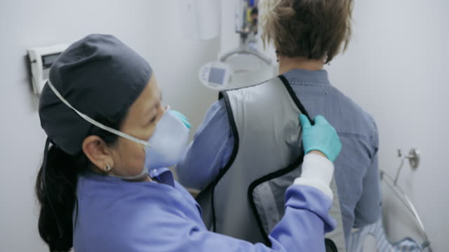 a latina dental hygienist in her fifties wearing a face mask straps a protective lead apron on to a woman in preparation for x-rays in a dental clinic - radiographer stock videos & royalty-free footage